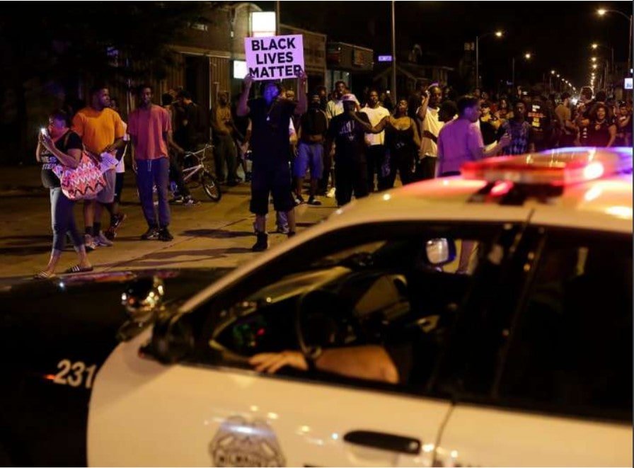 Demonstrators surrounding a police vehicle on Sunday as they protested the fatal shooting of Sylville K. Smith by an officer in Milwaukee.