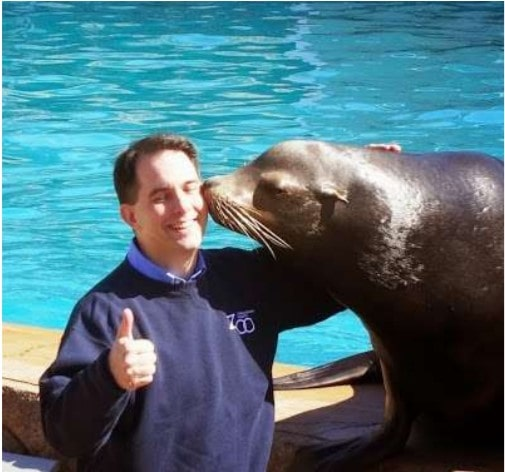 "Gov. Scott Walker gamely allowed a trained, 600-lb. sea lion named Slick to give him ""kisses"" Friday at the Milwaukee County Zoo, as part of Walker's promotion of tourism in Wisconsin."