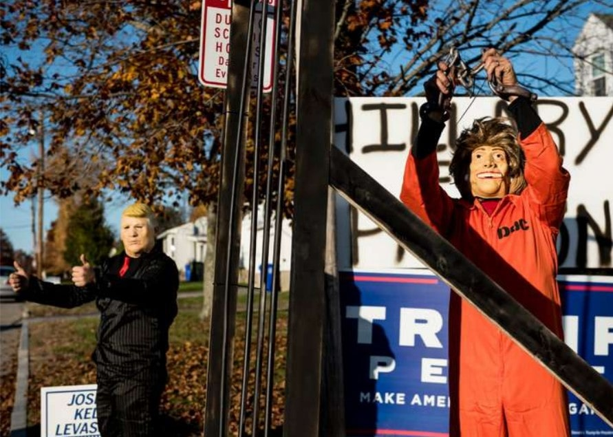 Dressed as the presidential candidates, Spencer Dumford, left, and Dan Shultz gestured to passing cars and people in the parking lot of a polling place in Manchester, N.H.